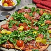 Pizza mit Rucola, Parmaschinken und Cocktail-Tomaten wie aus dem Steinofen